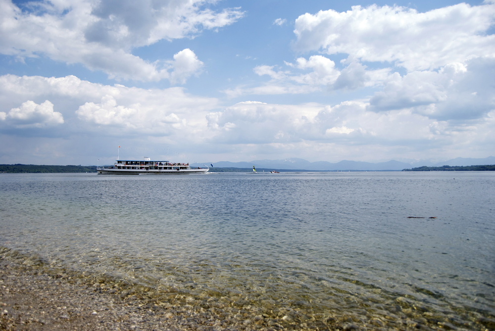 Un ferry cruza el lago con los Alpes al fondo