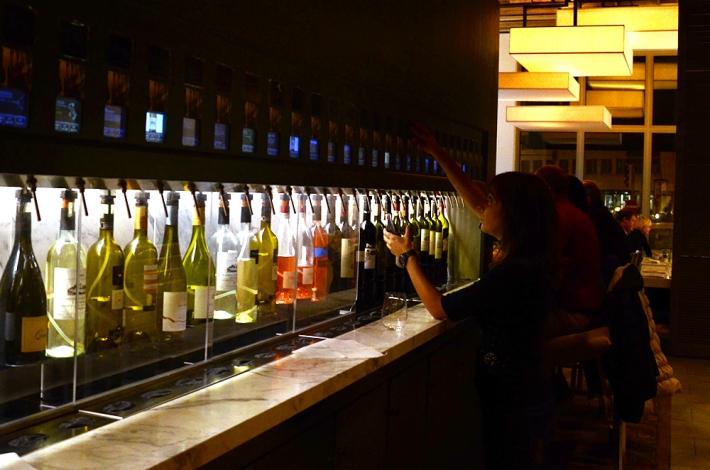 Sección de vinos en 'la Baracca' para elegir por copa, usando una tarjeta personal para el pago
