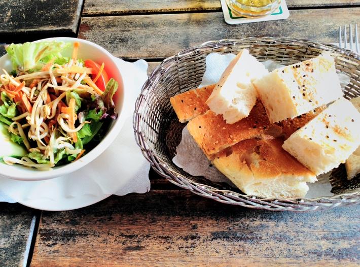 De entrada, una ensalada de hoja y pan, delicioso pan